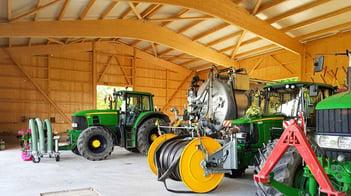 Freitragende Holzhalle gefüllt mit Traktoren und Maschinen.