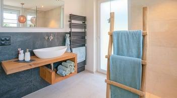 Trend-Badezimmer mit moderner Einrichtung, Holzelementen, blauen Tüchern und schwarzem Radiator