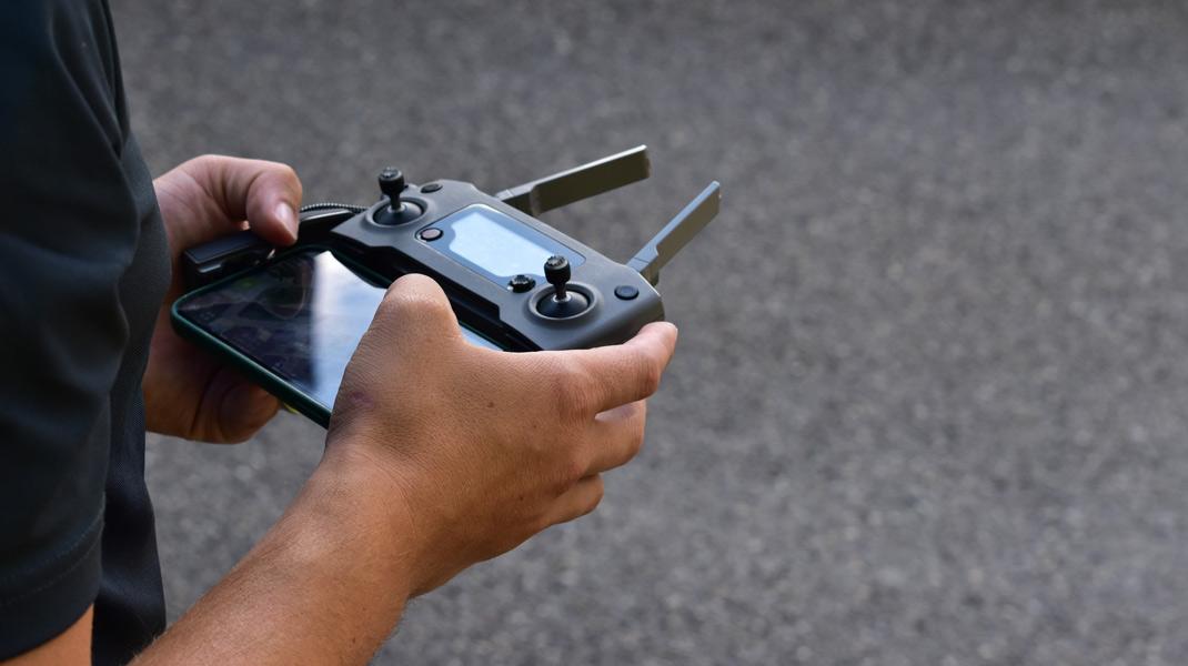 Hinter dem Steuer des Controllers einer Drohne – Profi beim Vermessen eines Gebäudes