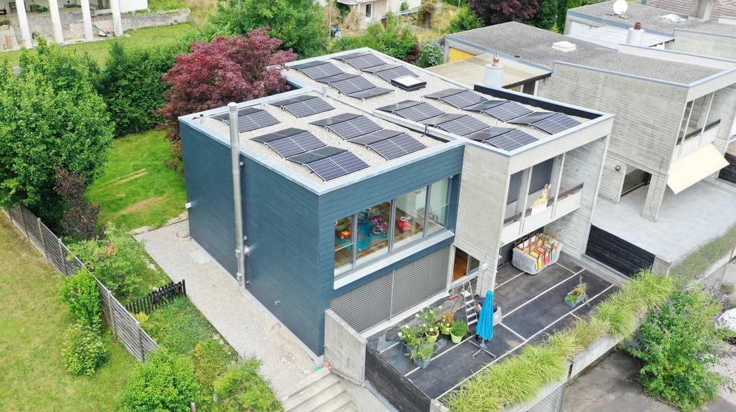 Reihenfamilienhaus in blauer Fassade und Betonoptik mit grünem Umschwung